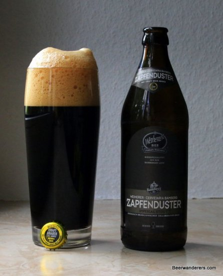 black beer with big tan head and bottle