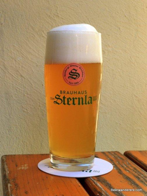 unfiltered golden beer in logo glass
