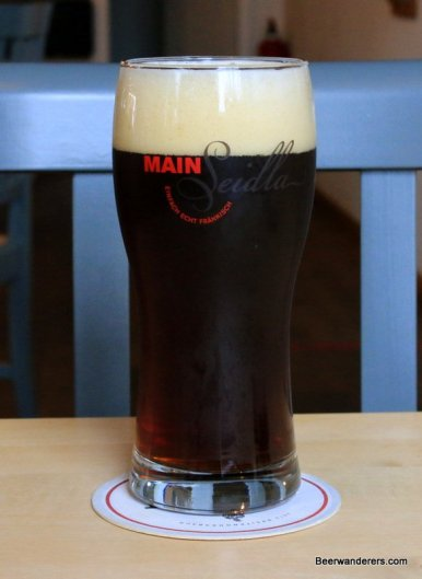 dark beer in glass with logo