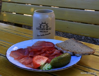 cold cuts on plate with beer in ceramic mug