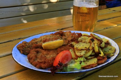 schnitzel with fried potatoes and golden beer in logo mug