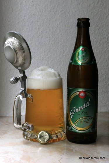 golden beer in mug with pewter lid and bottle