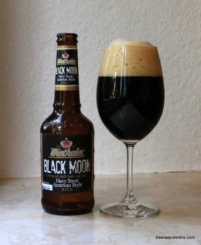 black beer with tan head in wine glass with bottle