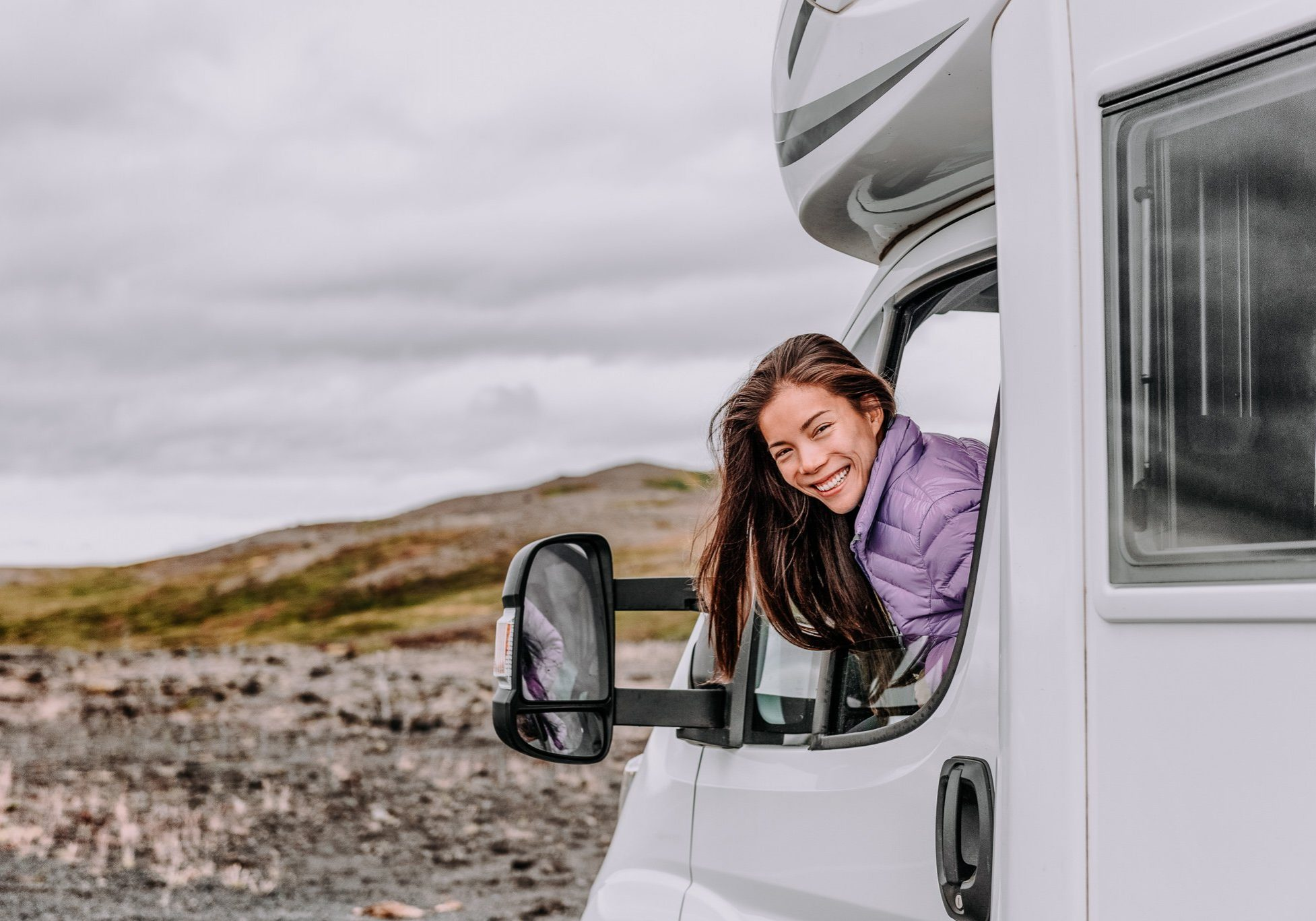 RV camper trailer travel woman driving motorhome camping van on Iceland road trip. Asian tourist driver smiling peeking out window of front seat