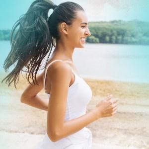 senhora a fazer exercicio na praia com aspecto saudavel e feliz