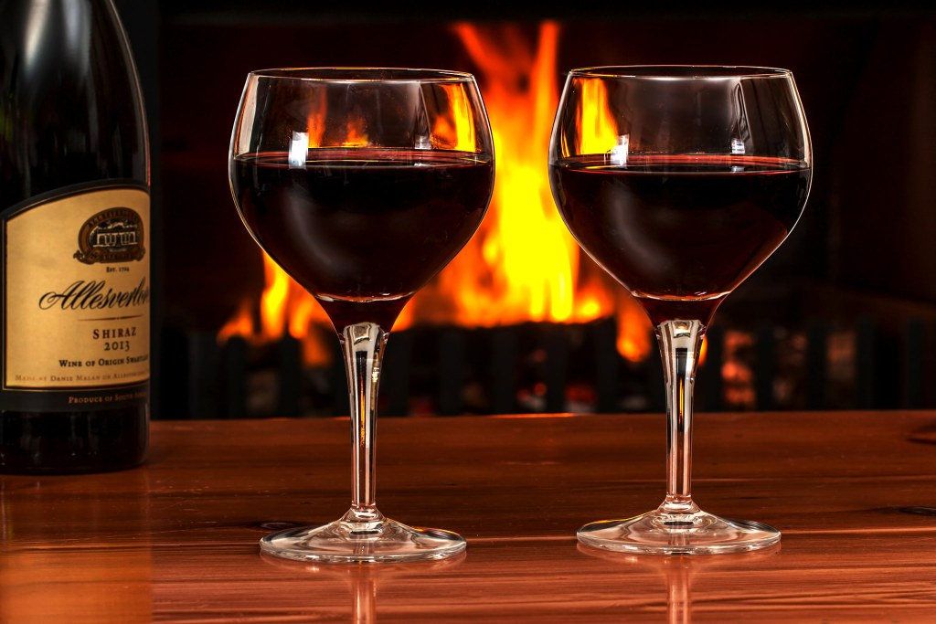Two glasses of white wine in front of a fireplace and a bottle of Shiraz