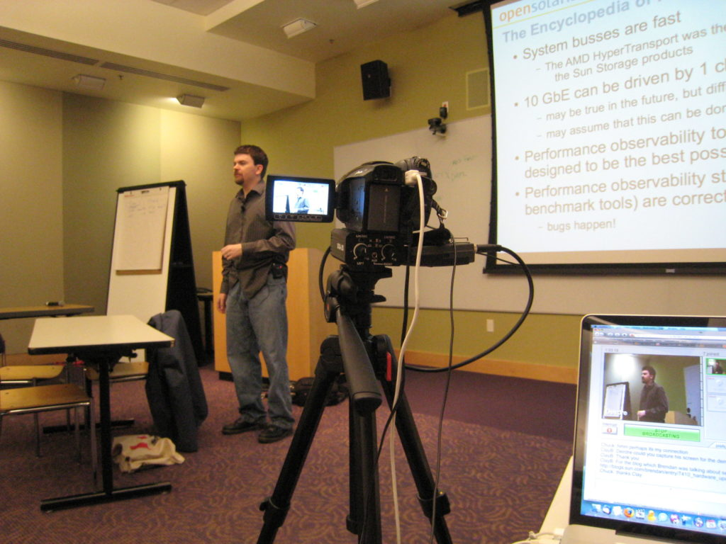 Brendan speaking in front of a projector screen, videocamera in the foreground