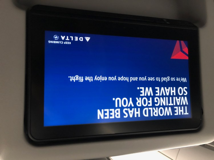 """sign on Delta's in-flight entertainment system saying """"The world has been waiting for you. So have we."""""""