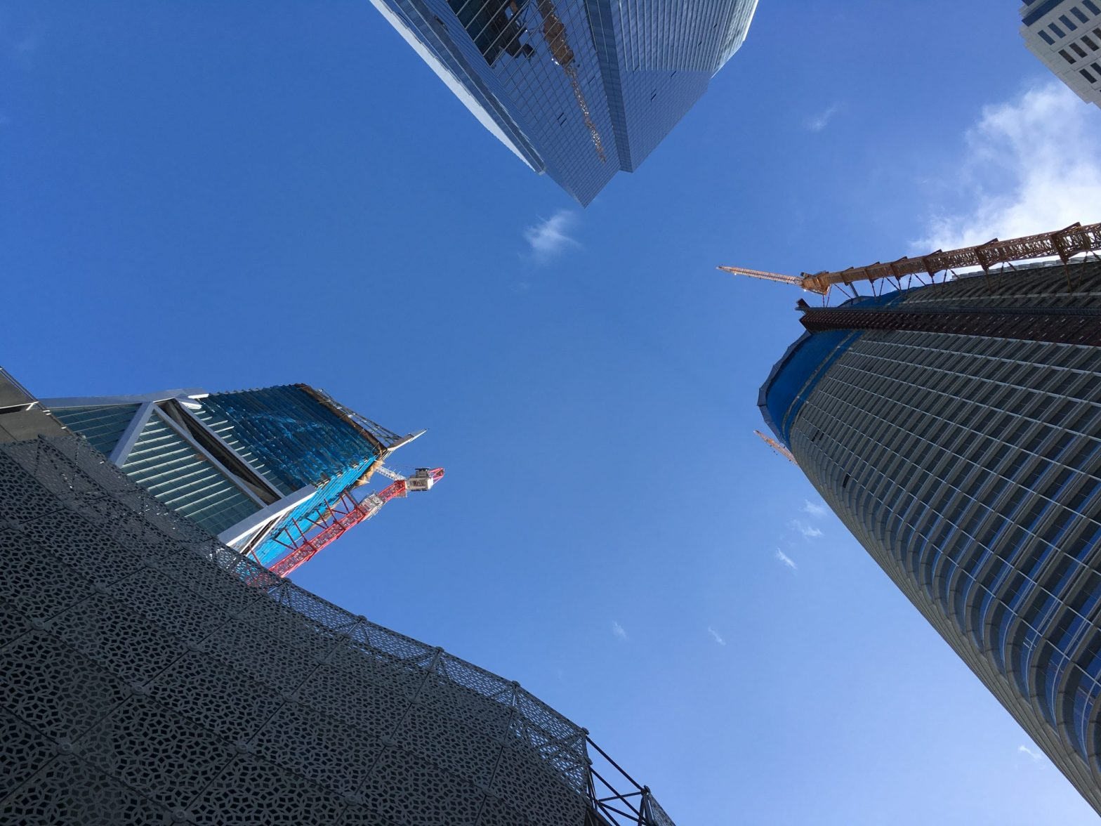 looking up between three tall buildings, two of them under construction