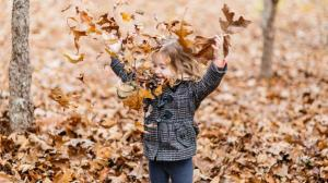 young-girl-playing-fall-leaves-081116-hero