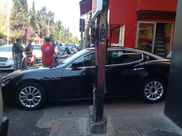 Police walk past illegally parked luxury car, despite ticket book in pants pocket.