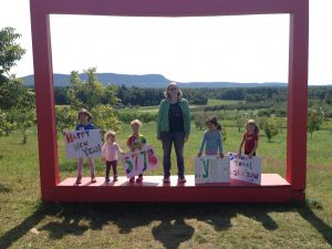 "Class standing in outdoor frame during ""Art in the Orchard"" visit."