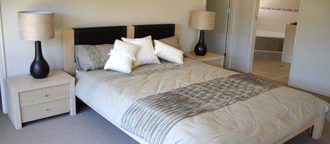 En el dormitorio una única cama con dos lámparas y mesillas simétricas