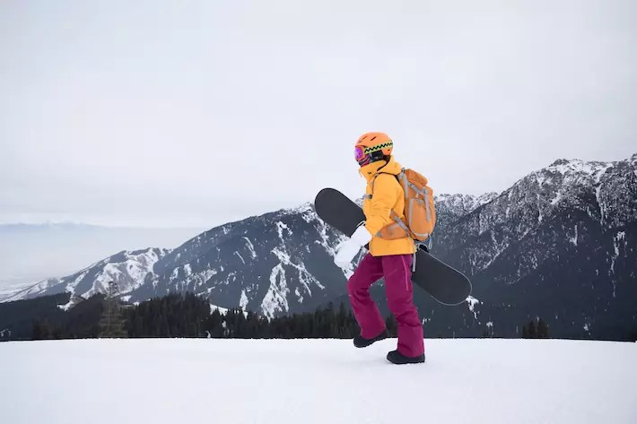 one snowboarder with snowboard walking on winter mountain top new zealand snowboard ski