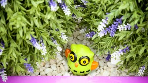 Small toy owl nestling in gravel under a flowering bush