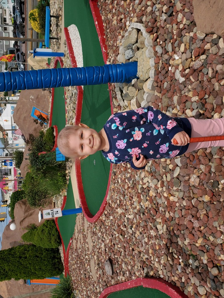 Young girl smiling enjoying putt putt golf while on a Believe In Tomorrow respite trip
