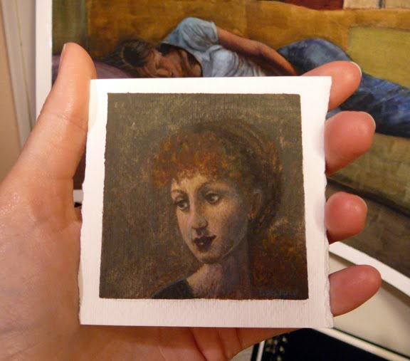 a hand holding a small card of watercolor paper with a miniature portrait of a woman's face