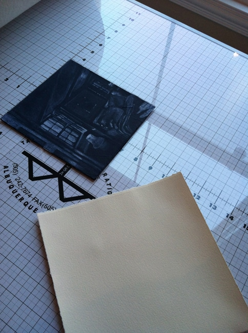 a silk aquatint plate, inked and wiped on the press bed, next to a sheet of paper, ready to print