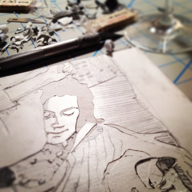 a mat board collagraph in process, showing a woman sleeping on a couch