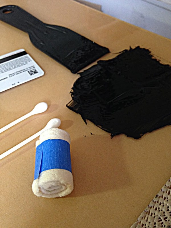 a spatula, and square of ink on a glass table top and a rolled peice of felt with a strip of masking tape around its belly to hold it closed and coiled
