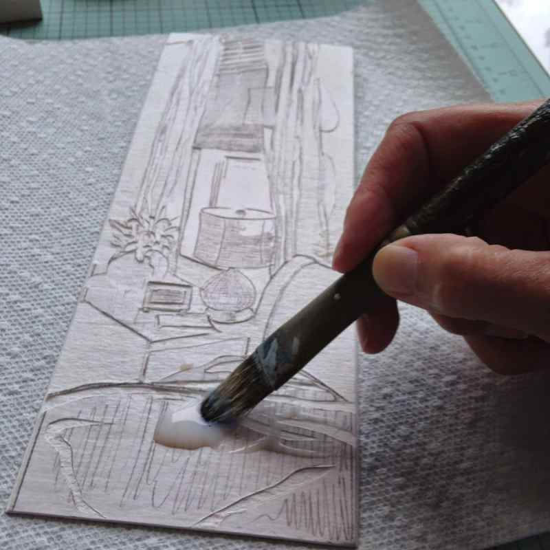 a bristle paint brush applying a clear gloss to the carved surface of the mat board