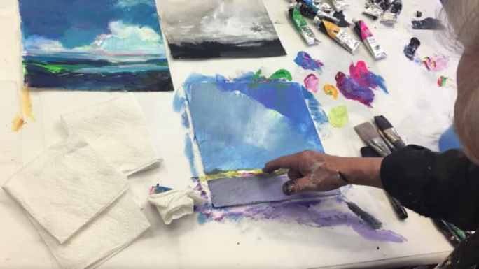 A man's hand scratching into wet paint on a festive, colorful sky-based landscape