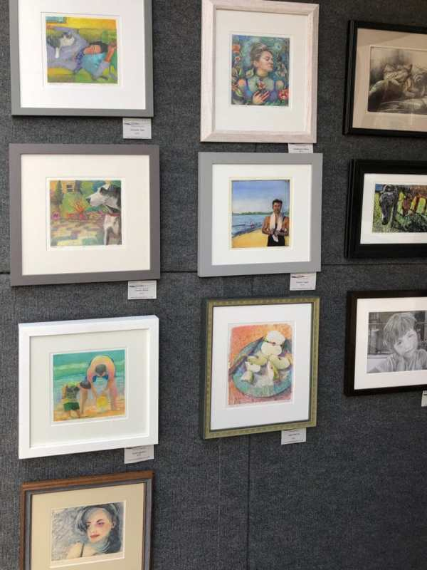 a printmaker's framed prints arranged in a booth at an art fstival