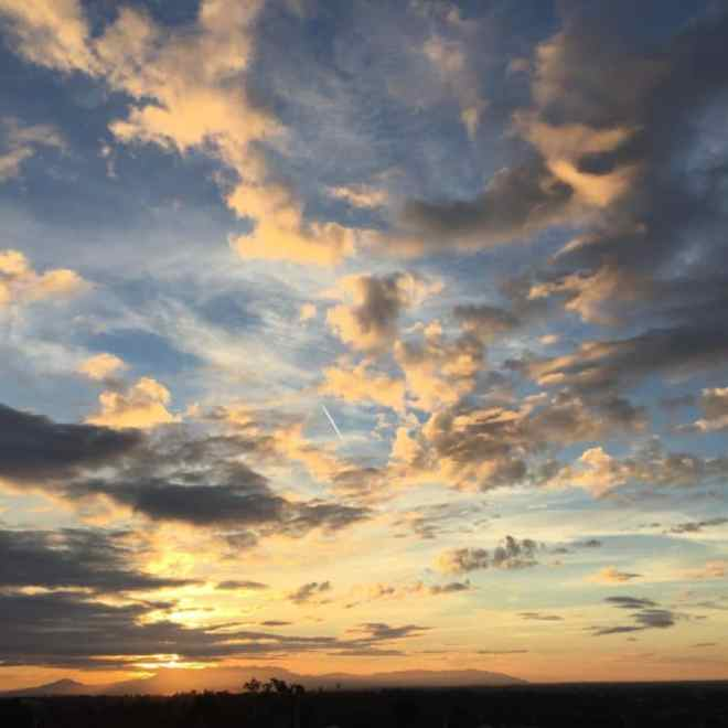 a horizon line with big blue sky dotted with peach and gray clouds