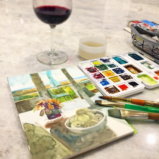 working on a watercolor at the kitchen counter with a small pad, a tiny portable palette of watercolors and a glass of wine