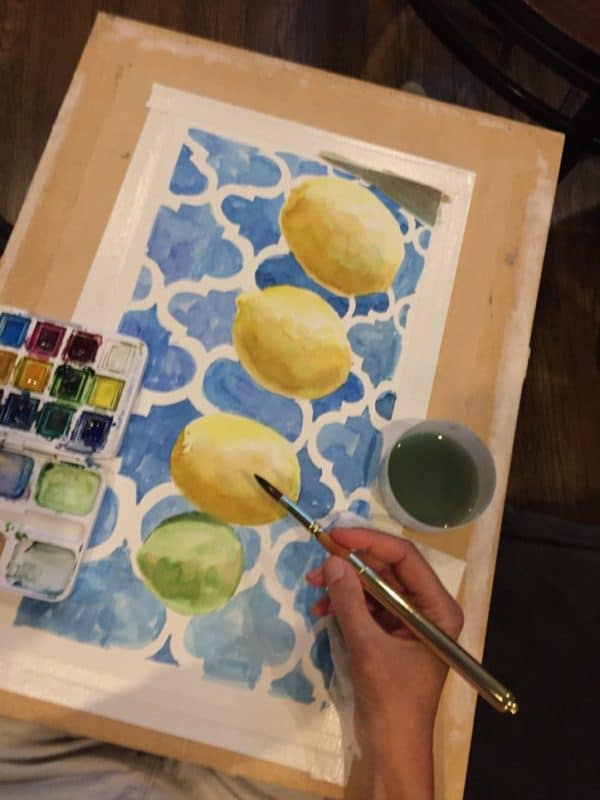 painting watercolor with a small palette and cup of water on a lap desk on the couch