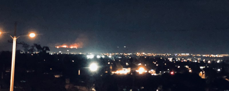 a night time horizon photo of ventura looking south at a mountain range on fire in the distance