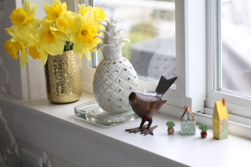 a window sill with yellow daffodils, a ceramic pineapple, a bird candle holder and two little patterned paper houses