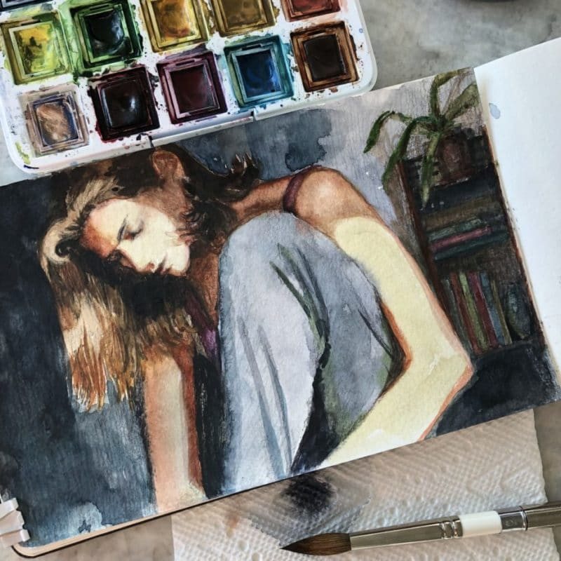 a watercolor painting in an open sketchbook of a girl in partial sunshine in a room with books behind her