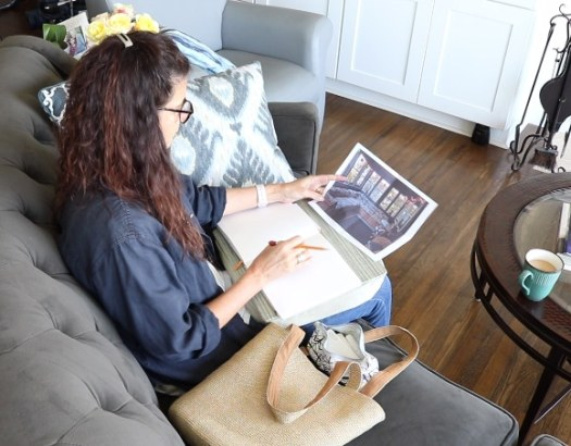 using a lap desk and a tote bag of supplies to make art on the couch