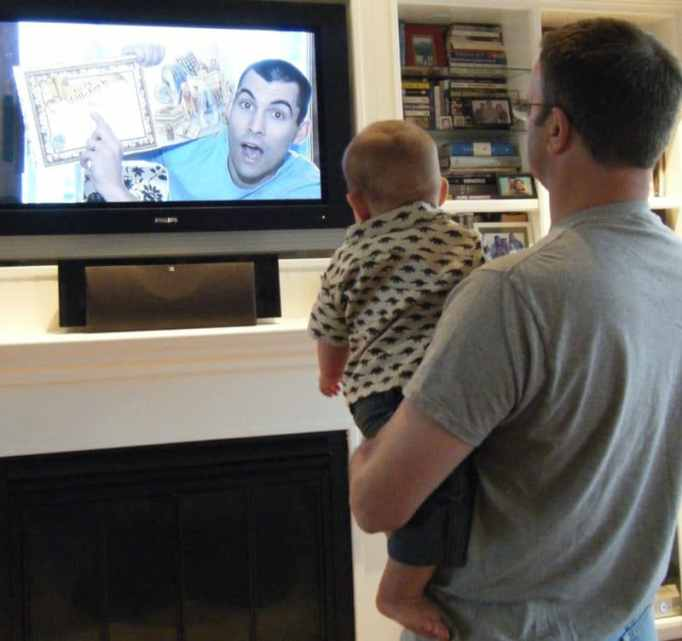 A soldier on a tv screen reading a storybook to an infant held by his grandfather