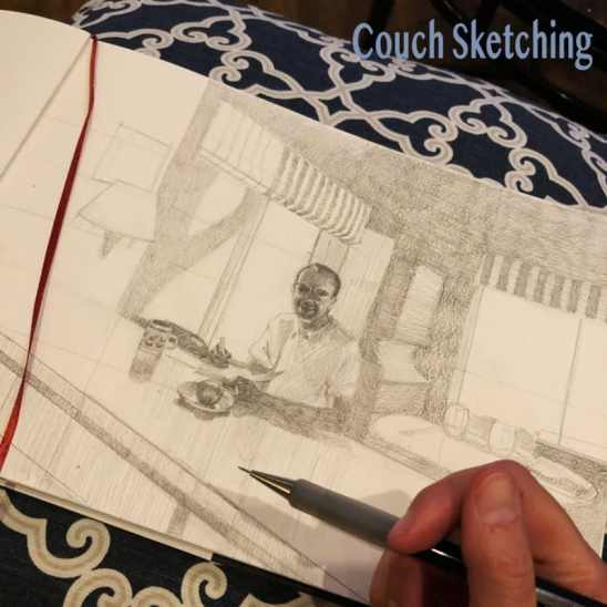 drawing in pencil of a man inside a cabin sitting at a counter, on a sketchpad propped on a pillow on my lap