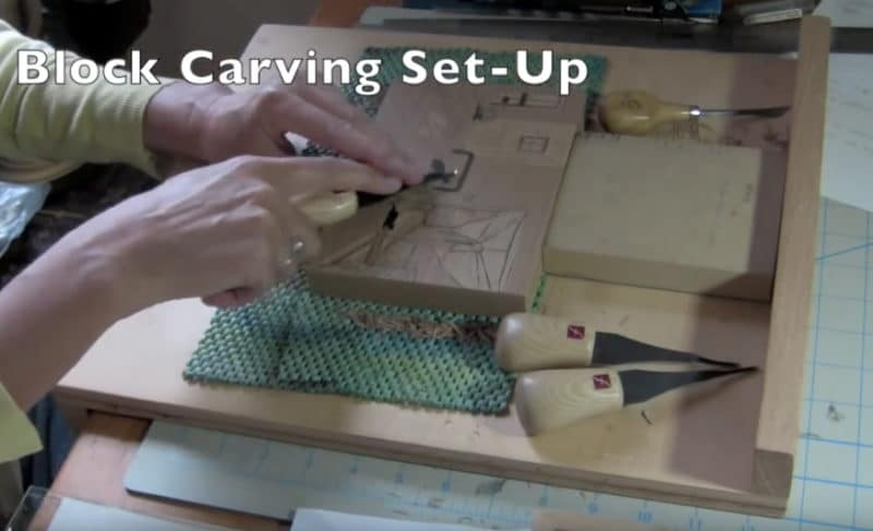 a block of linoleum being carved on a wooden bench hook