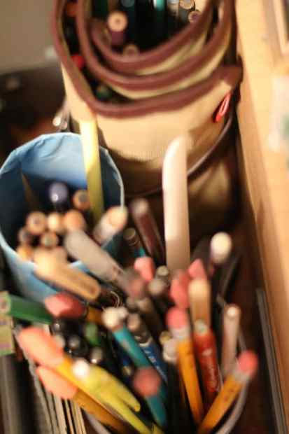 assorted pencils in an art studio, organized in containers