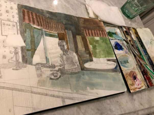 A sketchbook open on a kitchen counter, with watercolor palette and a cup of water, as the first washes of pigments are added to the pencil sketch
