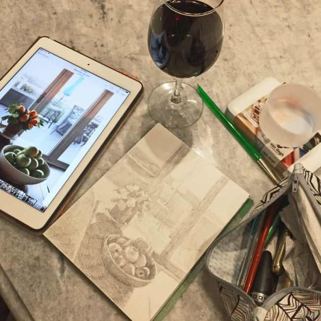 an ipad with a reference photo, a glass of red wine and a sketch in process