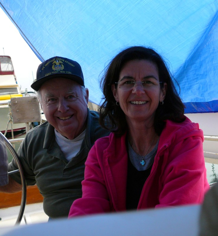 An older man, in a merchant marine cap, and a middle aged woman in a pink hoodie, sitting under a blue tarp in the cockpit of a sailboat.