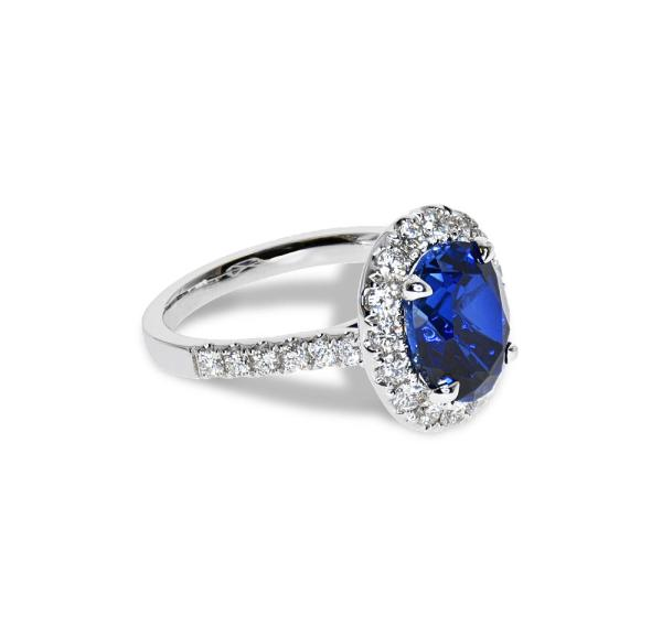 A white gold ring with a large sapphire and small diamonds