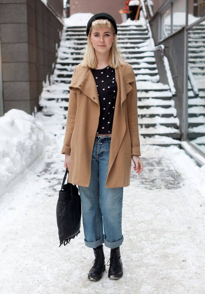 Woman with blonde hair wearing a polka dotted top with boyfriend jeans, tan coat, and ankle boots
