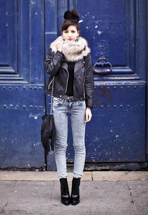 Woman wearing acid wash jeans, a black leather jacket, and black ankle booties with a faux fur collar