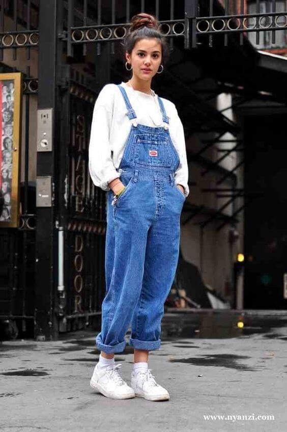 Woman wearing denim overalls, a white sweater, and white sneakers