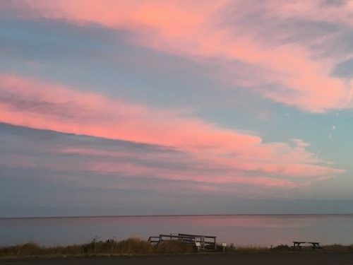 Pink sunset skies over the sea at Cocagne, New Brunswick.