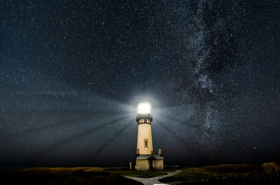 A lighthouse shines brightly in front of a starry backdrop at the Oregon coast.