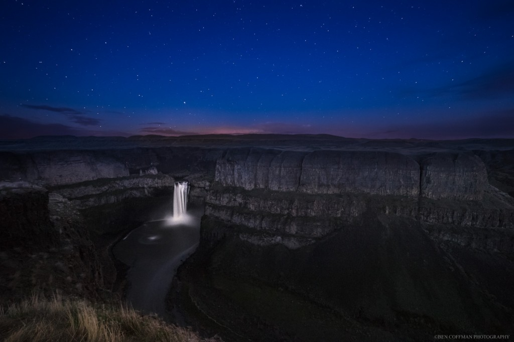 A waterfall flows as stars sparkle overhead, rural Washington state.