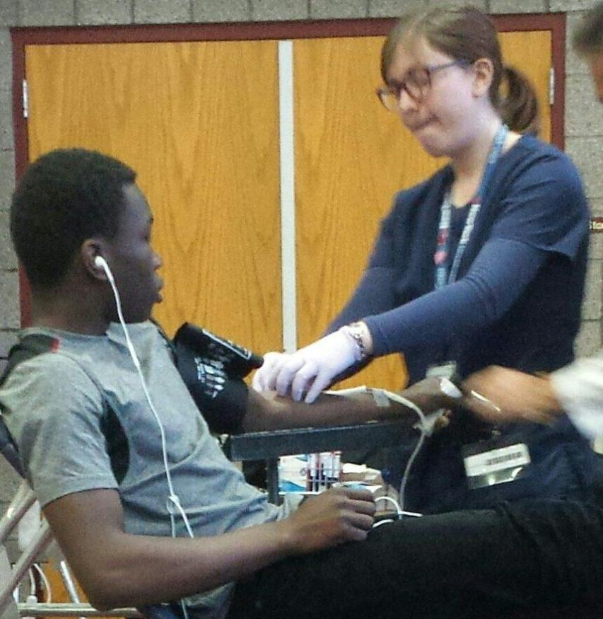 UDII Kukiele Kimonawoko getting assisted by a nurse, while she draws his blood.