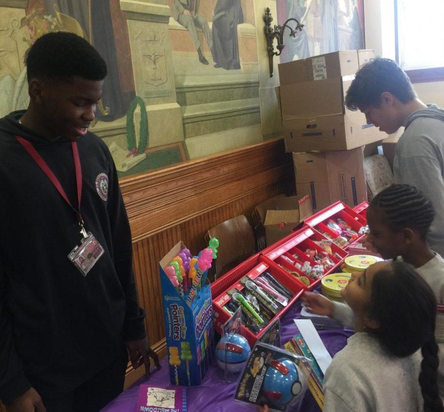 The Scholastic Book Fair returns and National Honor Society member, Chrisley Alexis, helps Jaya Garib purchase a Pokémon trinket.